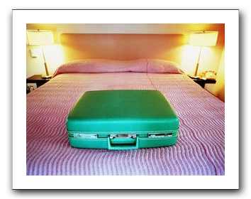 suitcase on a bed, looking lonely